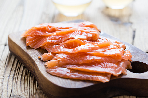 Smoked salmon on wooden board, sliced